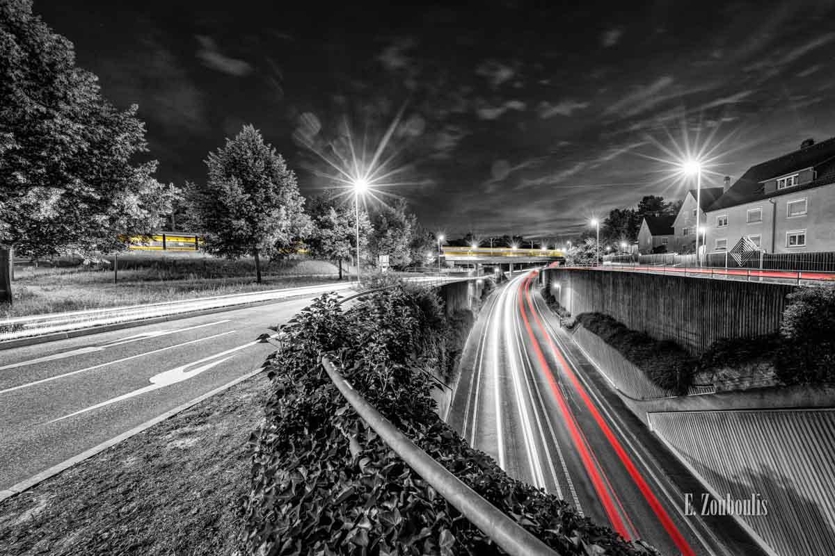 Der Verkehr nachts in Stuttgart Feuerbach. Autos mit roten und weißen Lichtern erhellen die Straße während eine gelbe Straßenbahn im Hintergrund die Brücke passiert