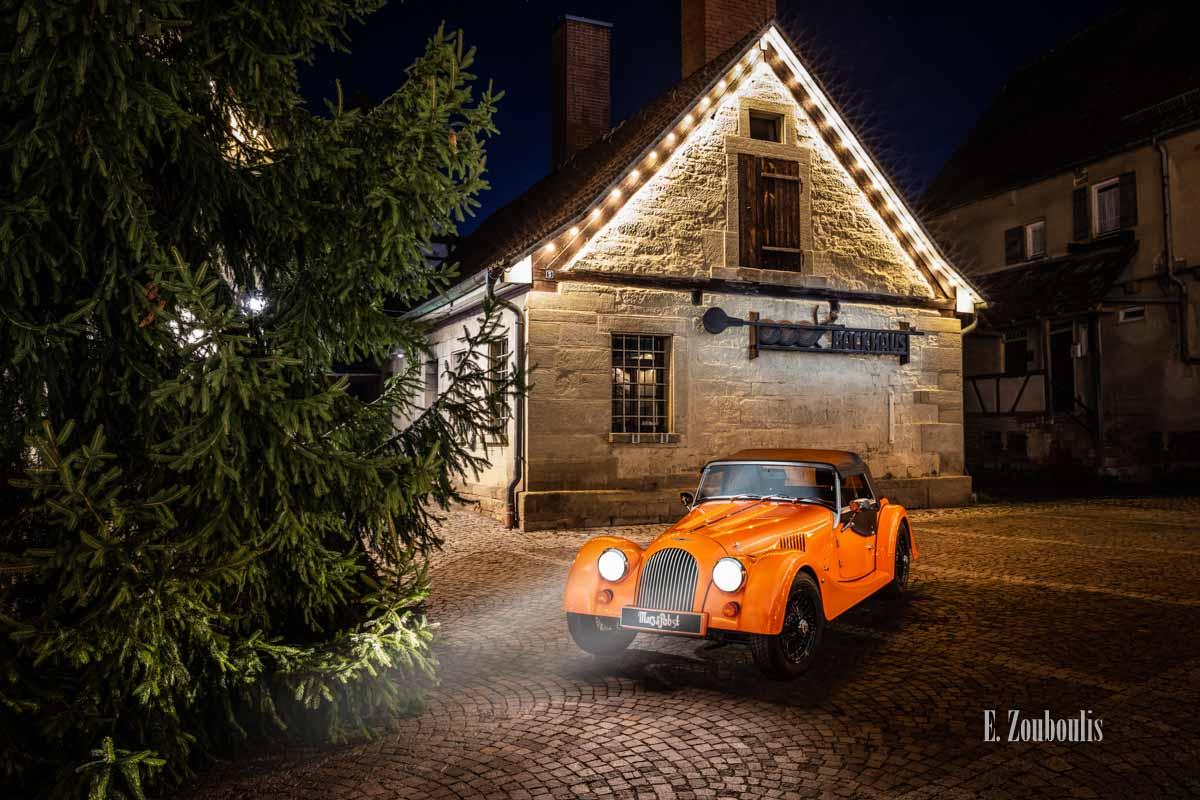 """Fotografie eines Morgan 4/4 mit seiner einzigartigen """"Morgan Orange"""" – Farbe vor dem Backhaus am Marktplatz in Gärtringen"""
