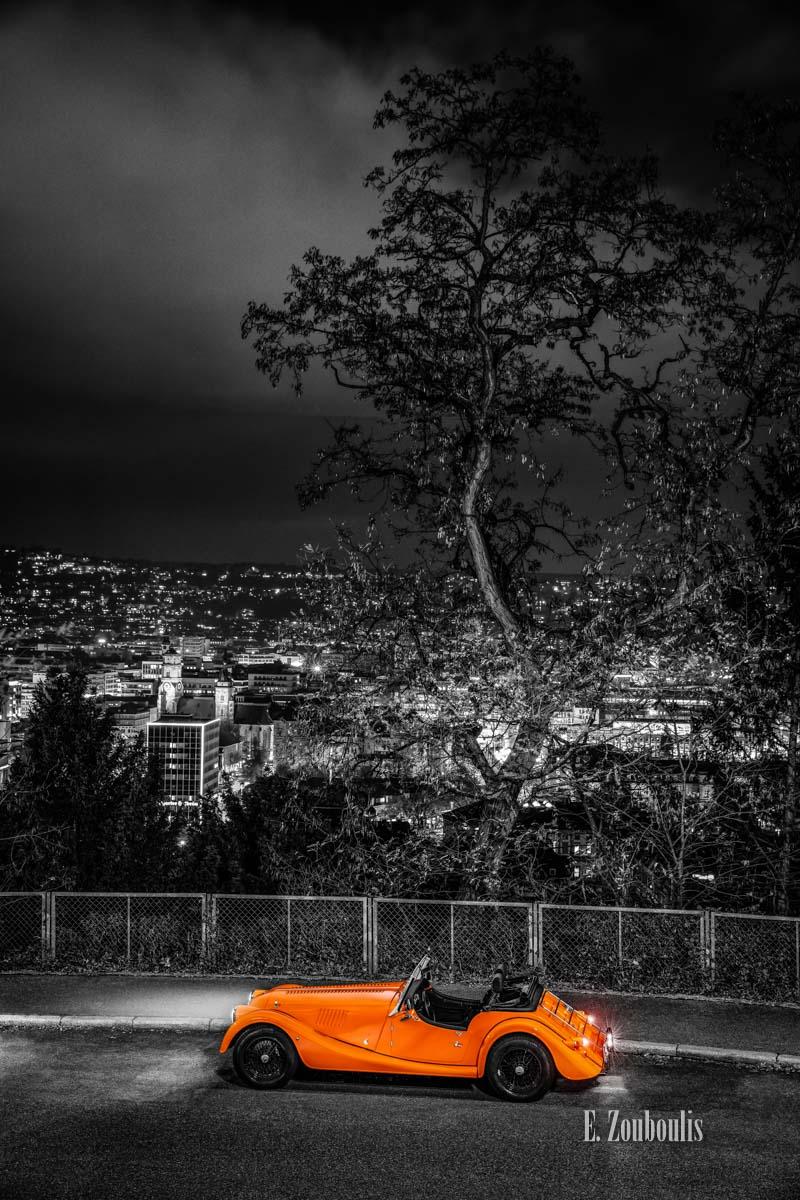 """Bild eines Morgan 4/4 mit seiner einzigartigen """"Morgan Orange"""" – Farbe an einem Aussichtspunkt in Stuttgart Dobel mit Blick auf die Stuttgarter Skyline"""