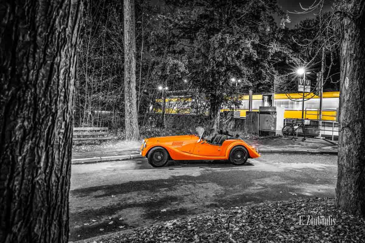 """Ein Morgan 4/4 mit seiner einzigartigen """"Morgan Orange"""" Farbe – vor einer vorbeifahrenden Straßenbahn in Stuttgart"""