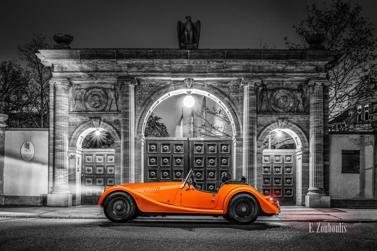 """Bild eines Morgan 4/4 mit seiner einzigartigen """"Morgan Orange"""" Farbe – vor dem Tor der Robert Bosch Stiftung in Stuttgart"""